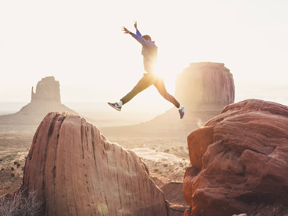 Man jumping from one rock to another