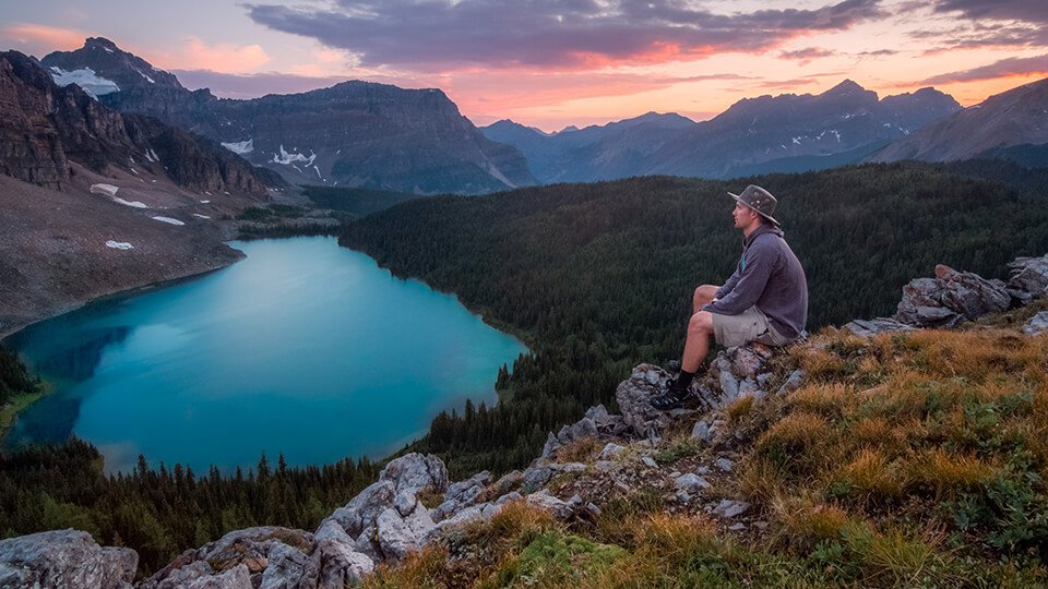 Man sitting on ridge, peacefully overlooking a still lake.