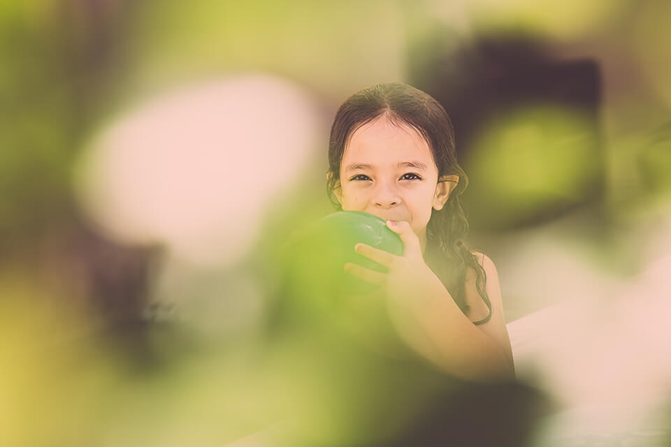 Smiling little girl blowing up green balloon