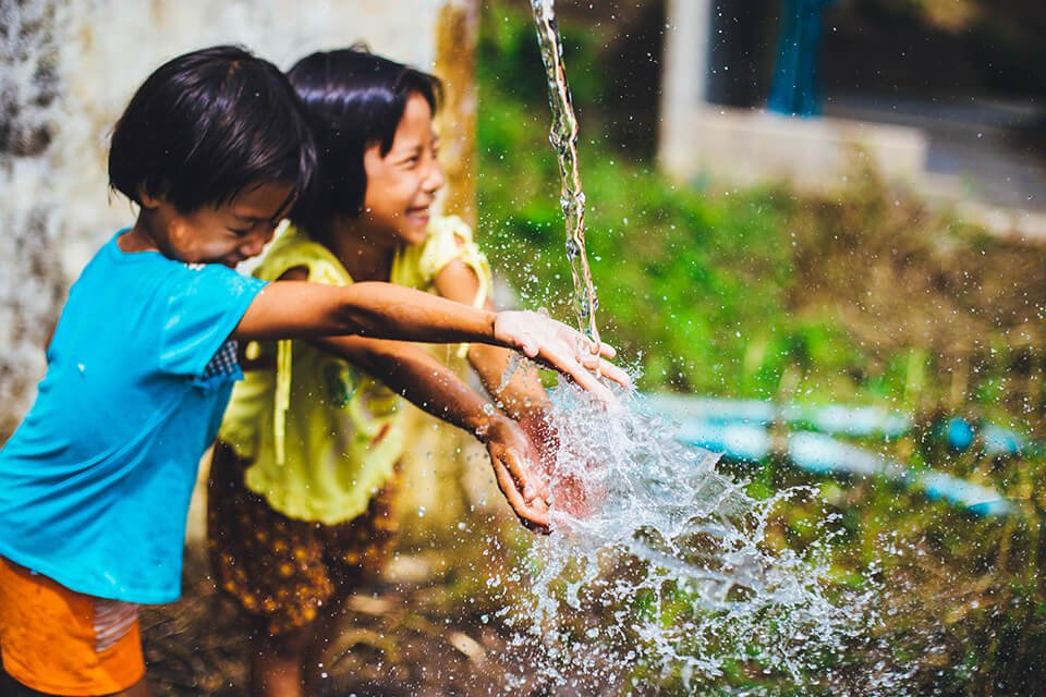 Children laughing and playing with water