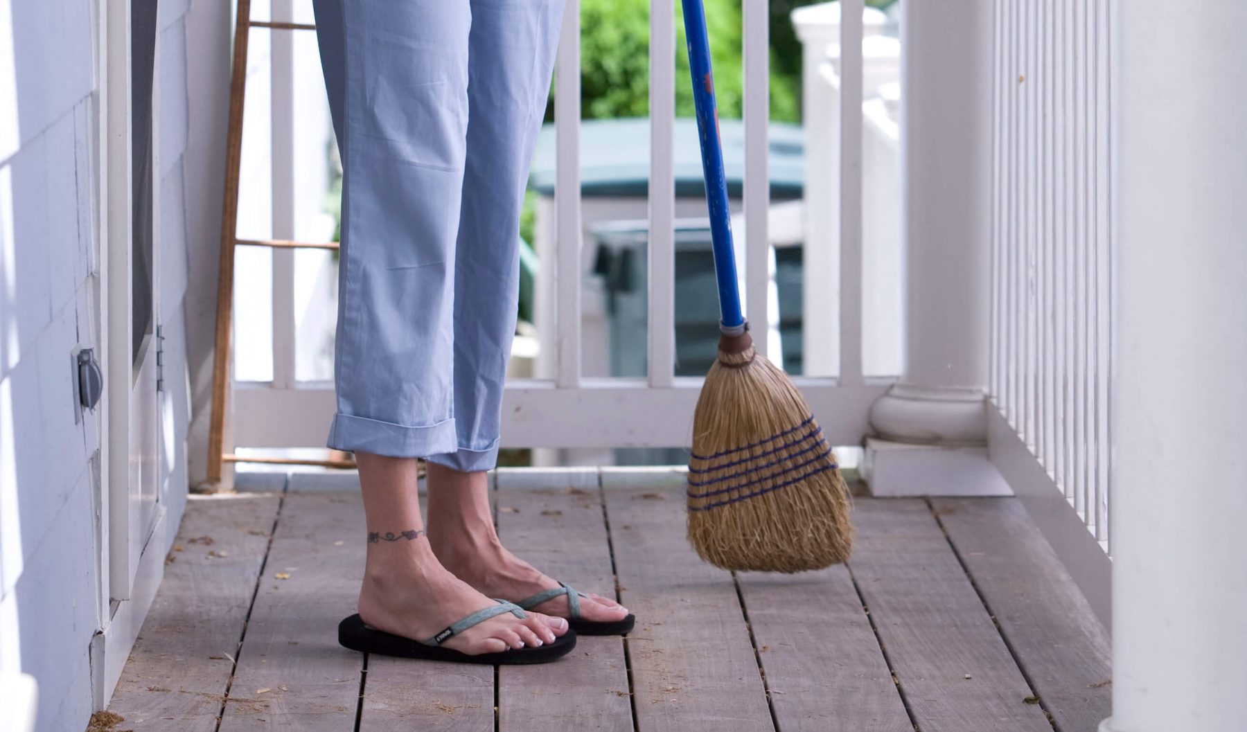Woman sweeping her porch with a broom.