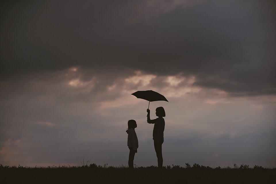 Girl holding up umbrella for little sister