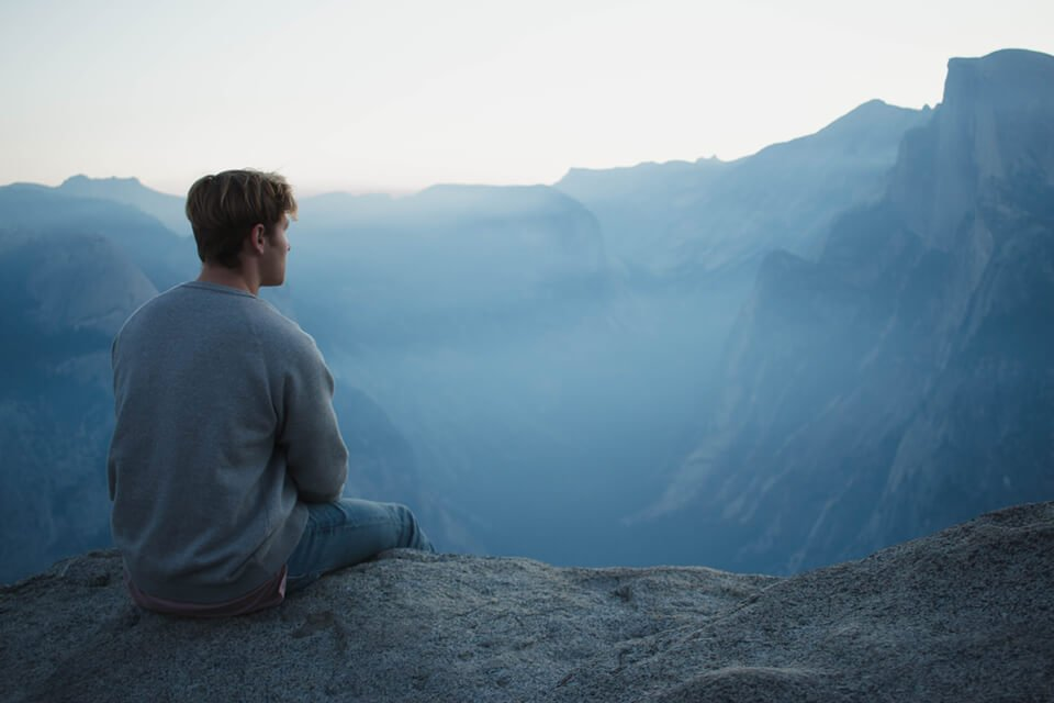 Young man in sweater sitting over edge of cliff admiring the scenic landscape