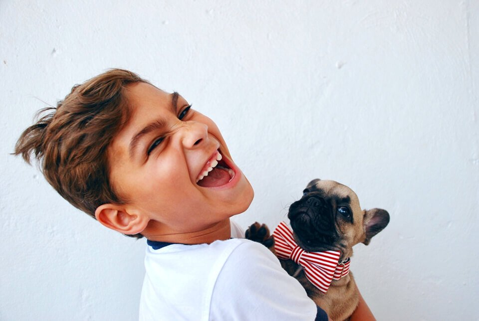 Child looking back laughing while holding a puppy