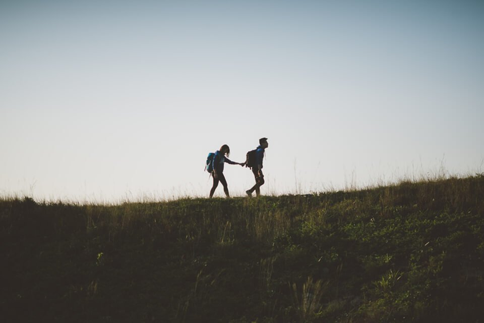 Man leading a woman, hand-in-hand, on a hike