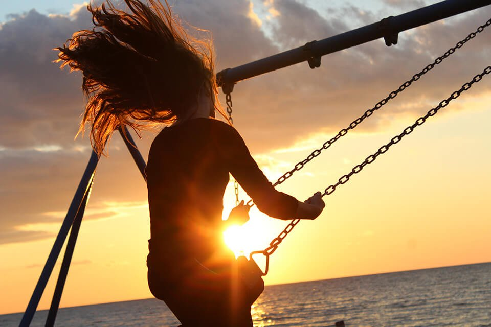 Woman happily swaying on a swing set near a sunset