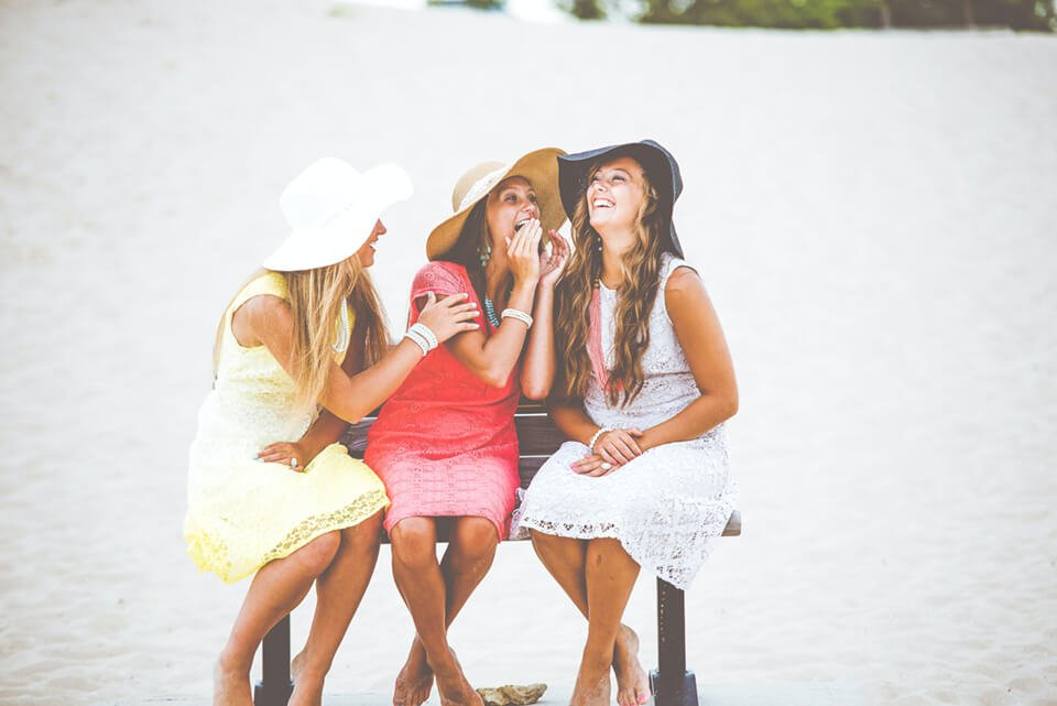 Group of women laughing together on a bench outside
