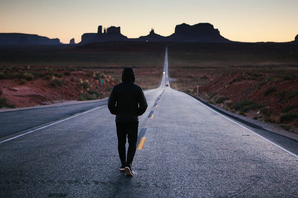 Man walking down an empty road with his hoodie on