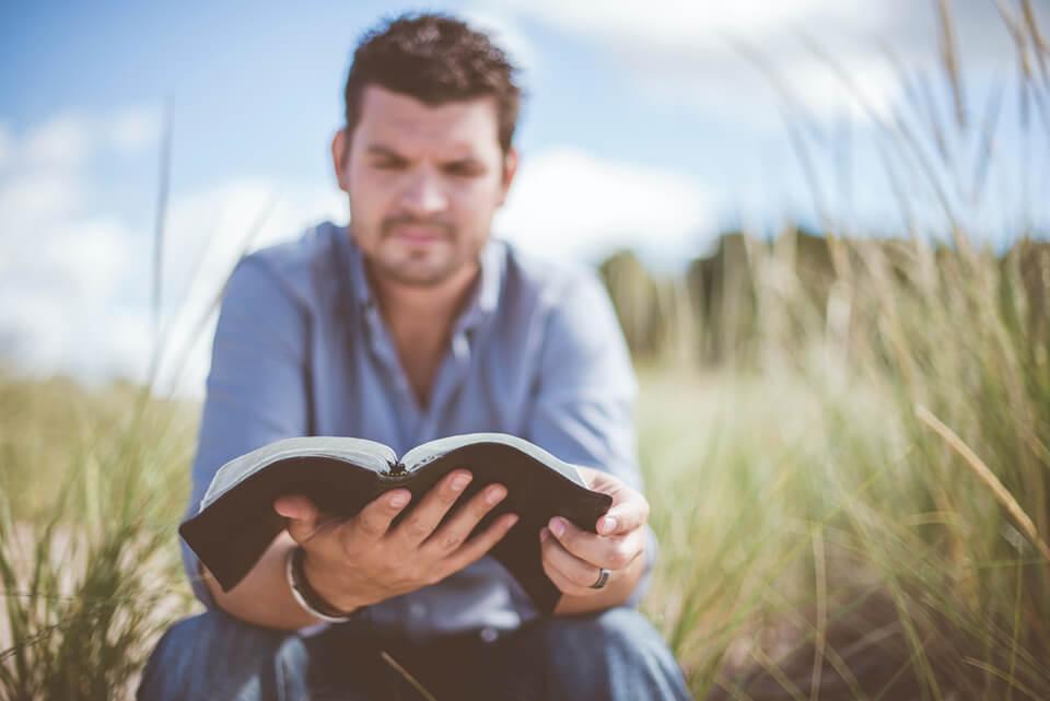 Man sitting outside, reading his gratitude journal