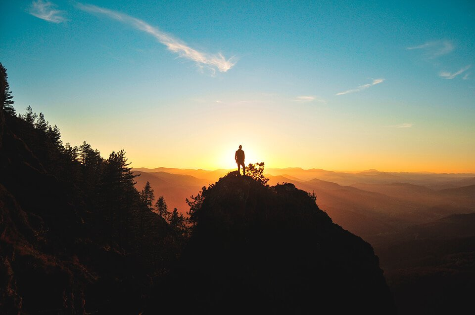 Man looking at sunset from top of hill