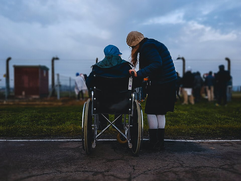 Woman helping out elderly man in wheelchair
