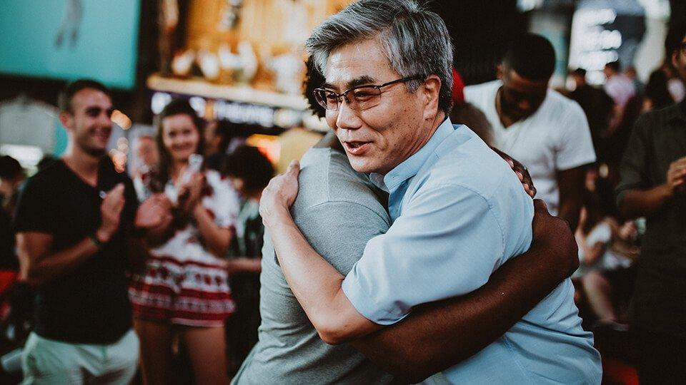 Two men hugging in the street