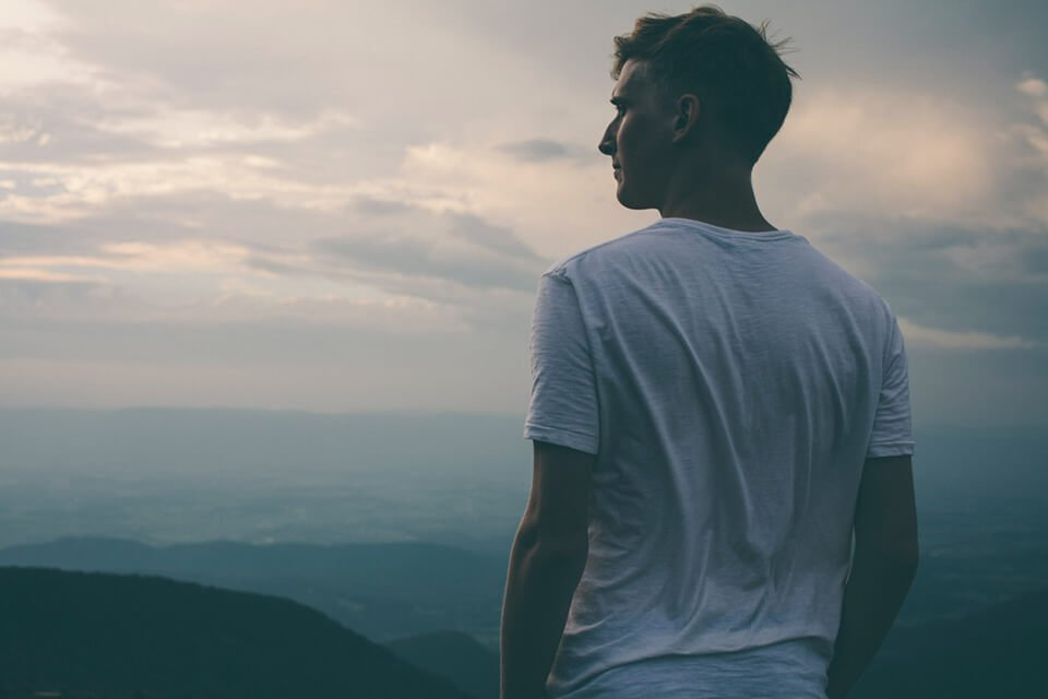Man looking off into the distance over a hilly vista