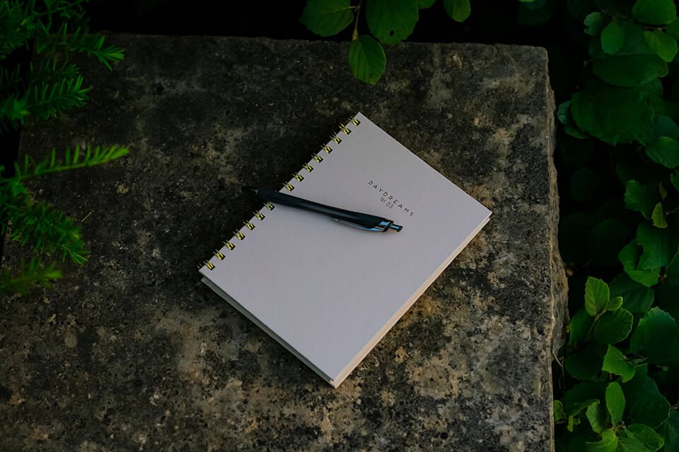 Journal with pen laying on a stone bench outdoors