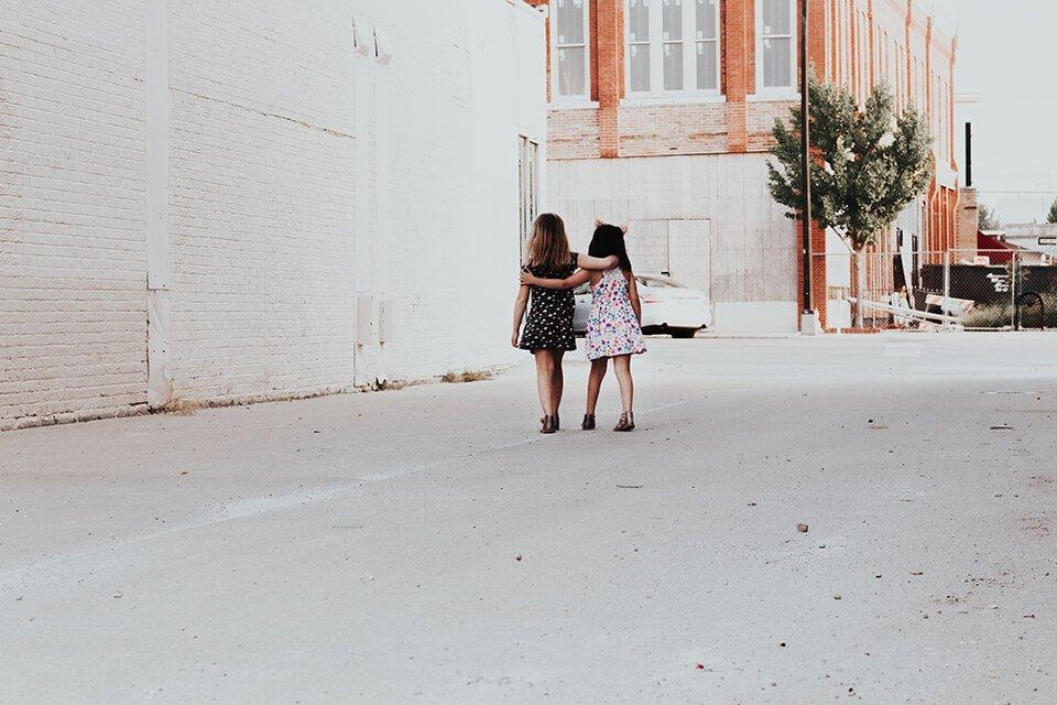 Two little girls walking arm in arm