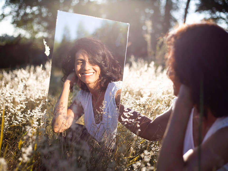 Woman looking at herself in the mirror in a field