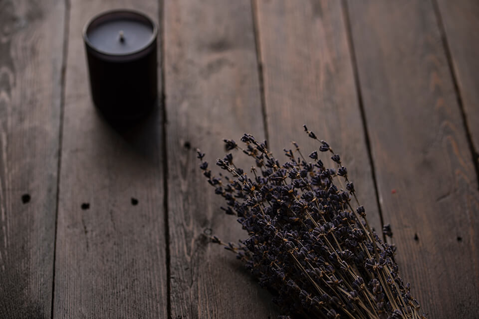Lavender candle and plant laying on table