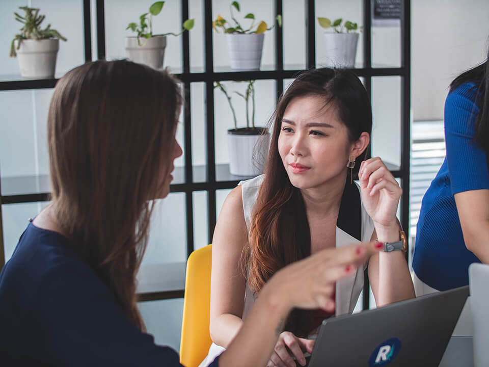 Woman listening to her colleague explaining a problem