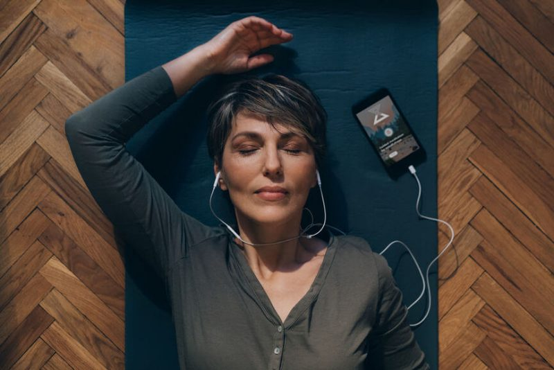 Woman laying with eyes closed, listening to guided meditation app