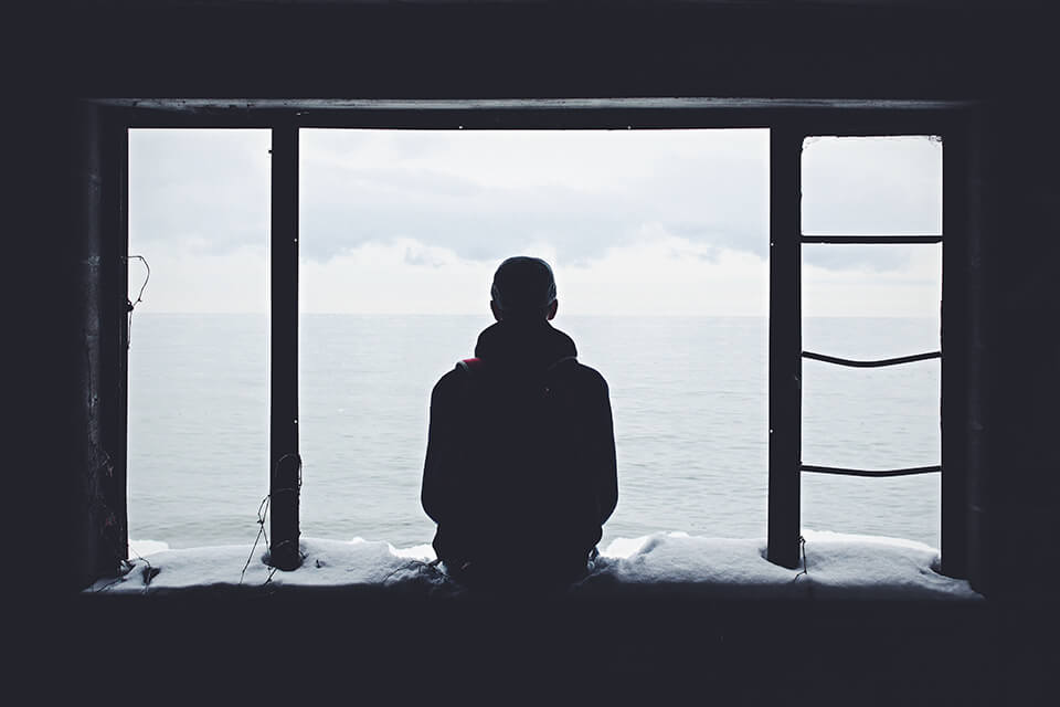 Man sitting on a window ledge looking at the water