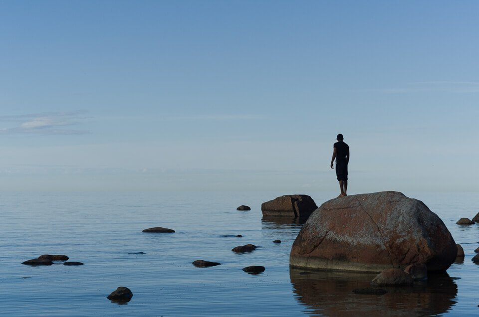 Man standing on a rock, alone in the middle of the water