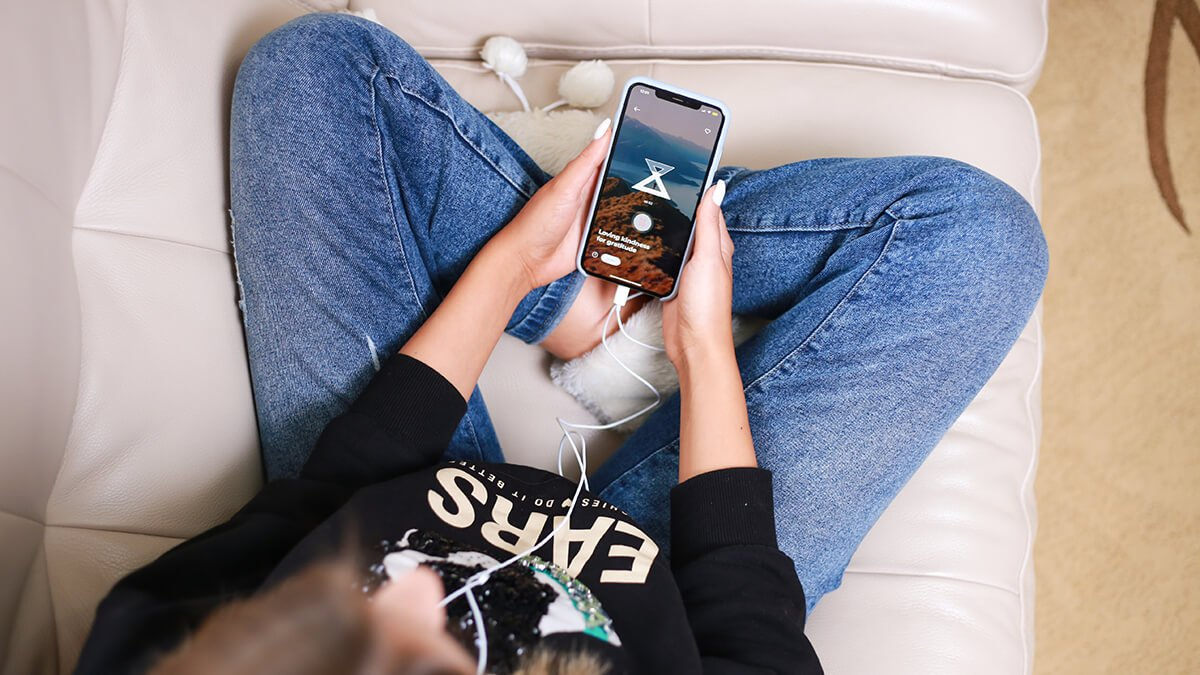 Woman sitting on couch listening to guided meditation with phone in lap