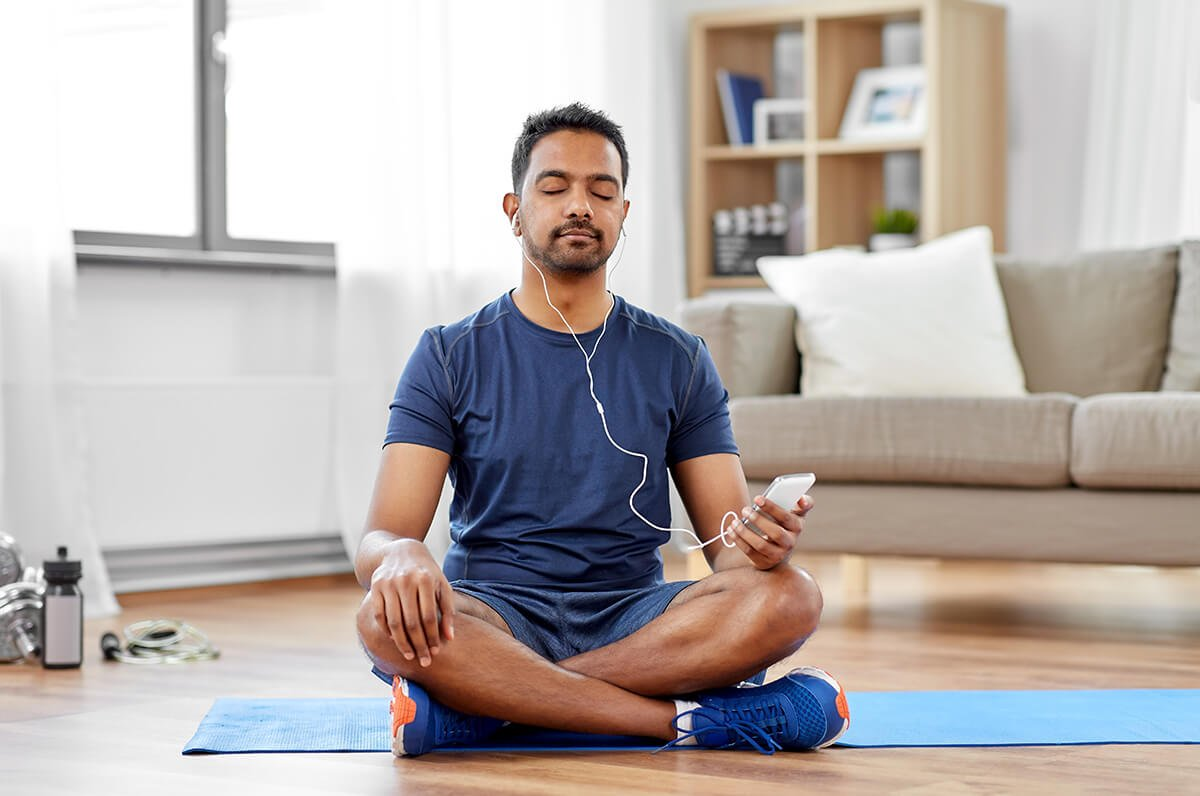 Man sitting on yoga mat, listening to guided meditation app