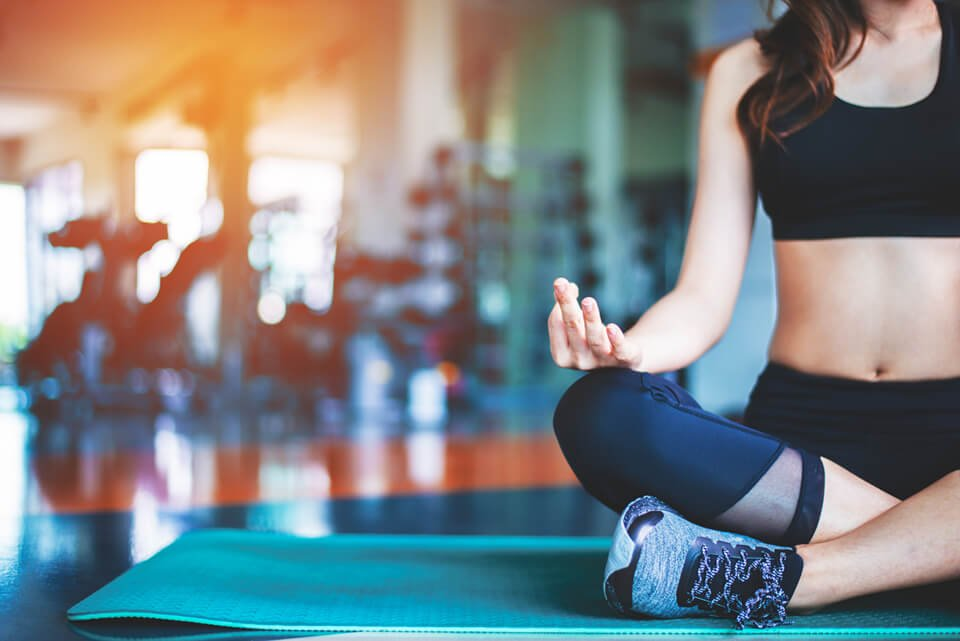 Woman sitting on yoga mat in gym meditating