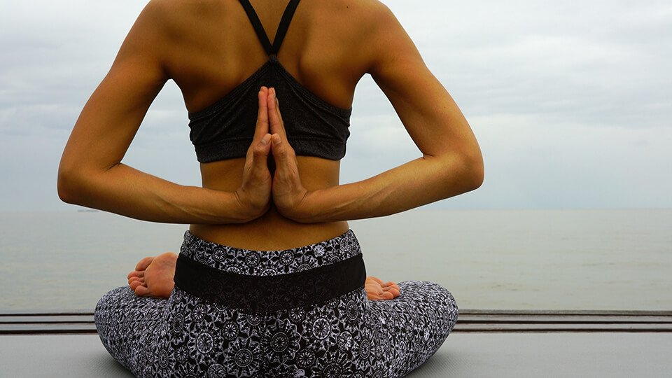 Woman sitting and meditating wearing meditation clothing