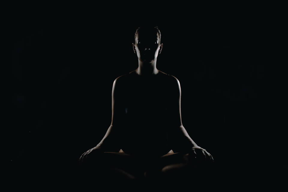 Woman sitting and practicing meditation in the dark