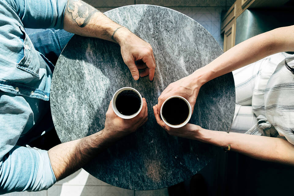Two people sitting at a table having a coffee