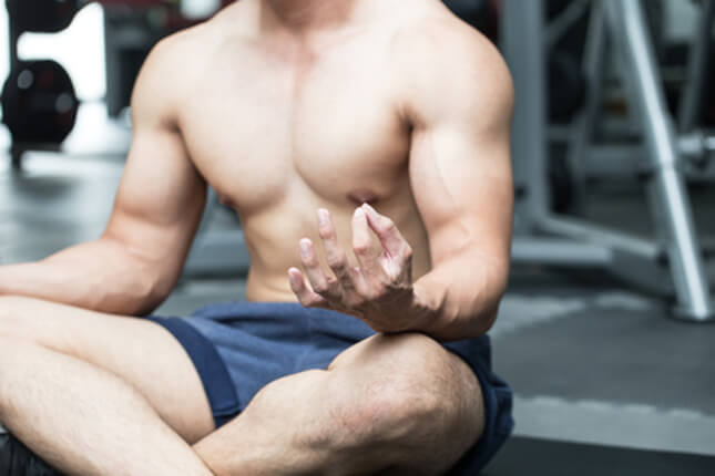 Man sitting in weight room of gym meditating