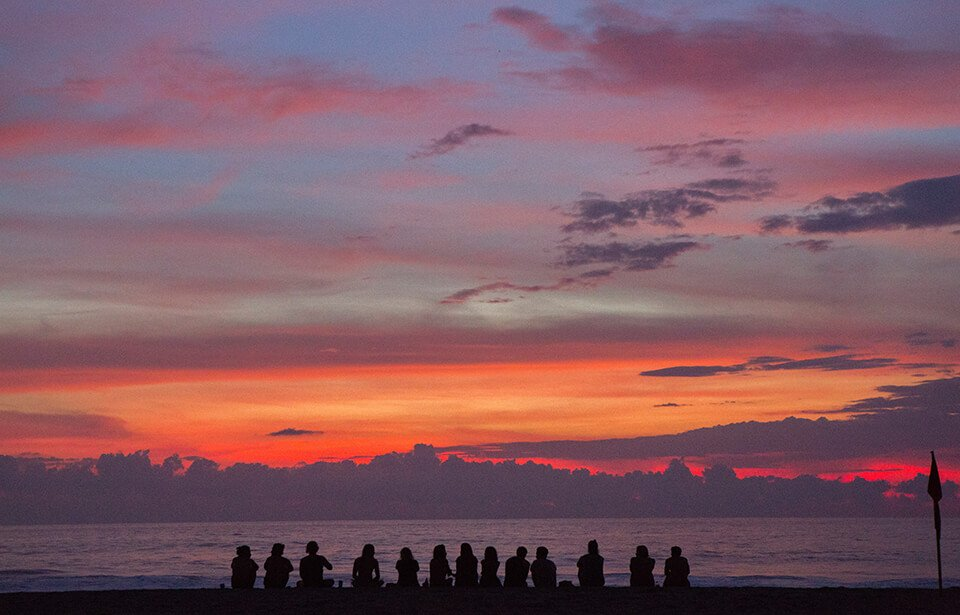 Group of people meditating by a beach