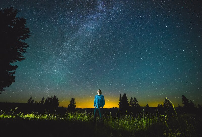 Man lost in thought in scenic night landscape