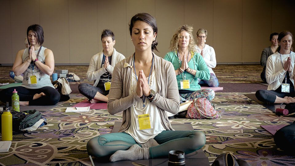 Group of people sitting and meditating at a conference