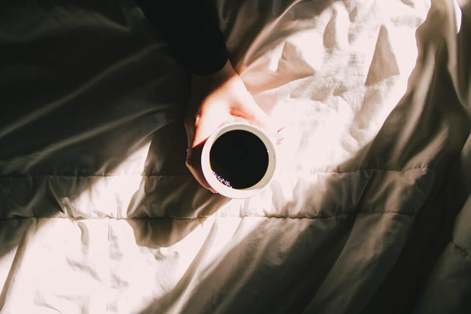 Cup of coffee held out over bed