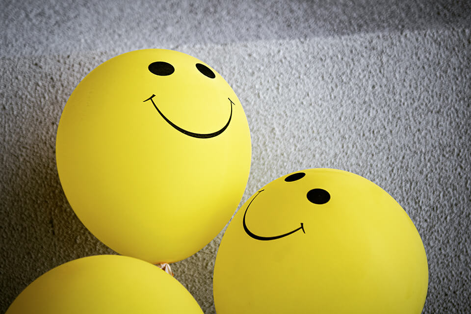 Three bright yellow balloons with smiley faces on them