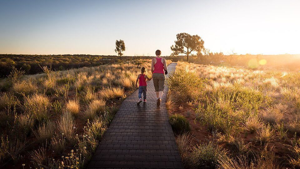 Father walking down path with daughter near the setting sun