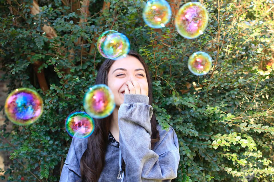 Woman covering her mouth laughing with bubbles floating around her