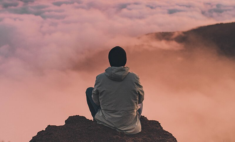 Man sitting on edge of cliff, overlooking clouds in the distance