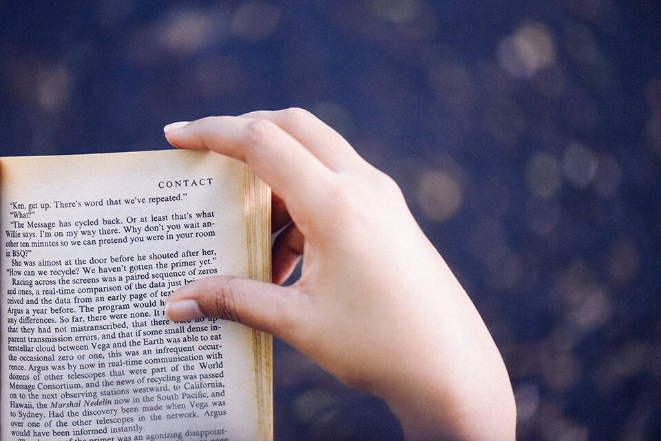Person reading a book outdoors