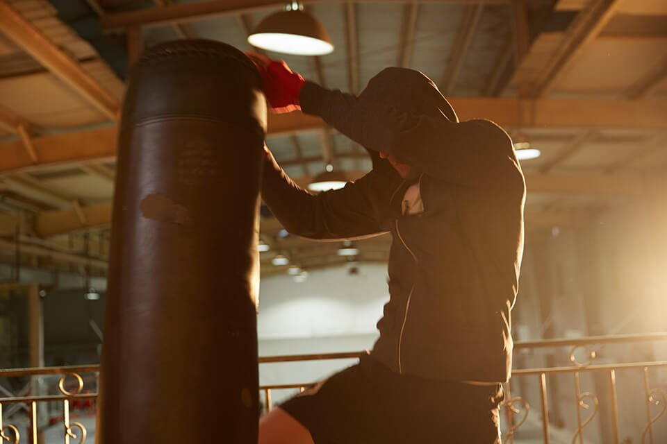 Man in hoodie beating up heavy bag as an outlet for his anger
