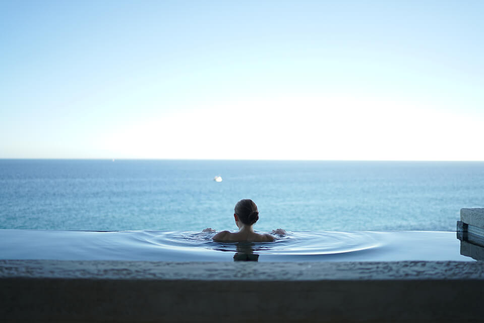 Woman in edgeless pool achieving inner peace