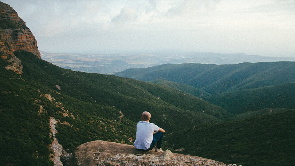 Man sitting on top of hill contemplating