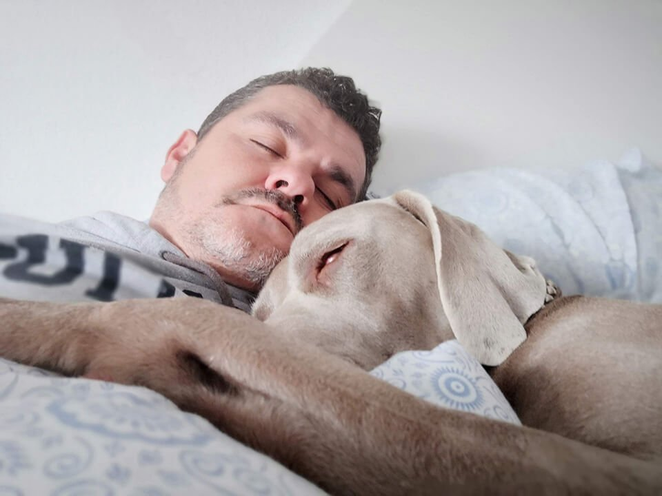 Man sleeping in bed with his dog