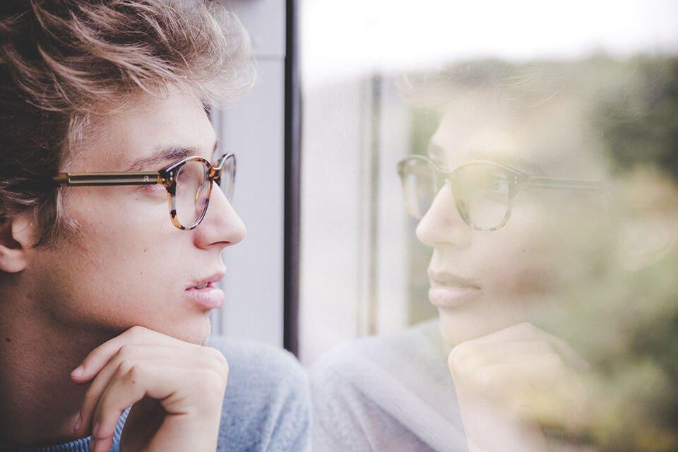 Man staring into window on train