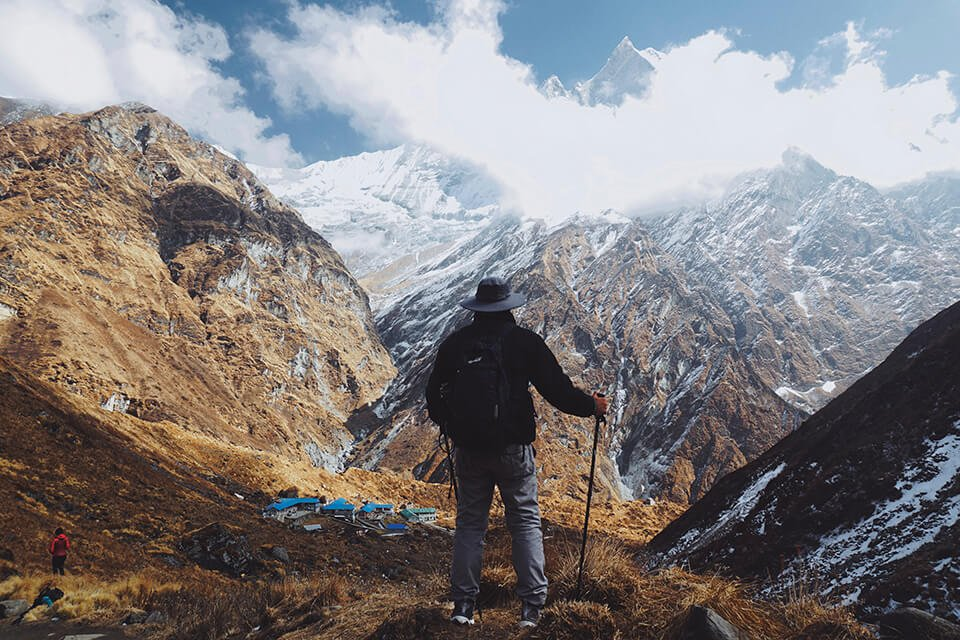 Man in hiking gear overlooking a vista from the top of a mountain