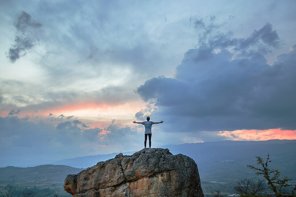 Man standing triumphantly on top of rock