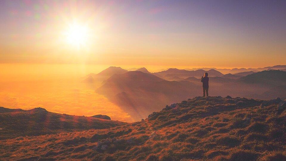 Woman taking a photo of the setting sun