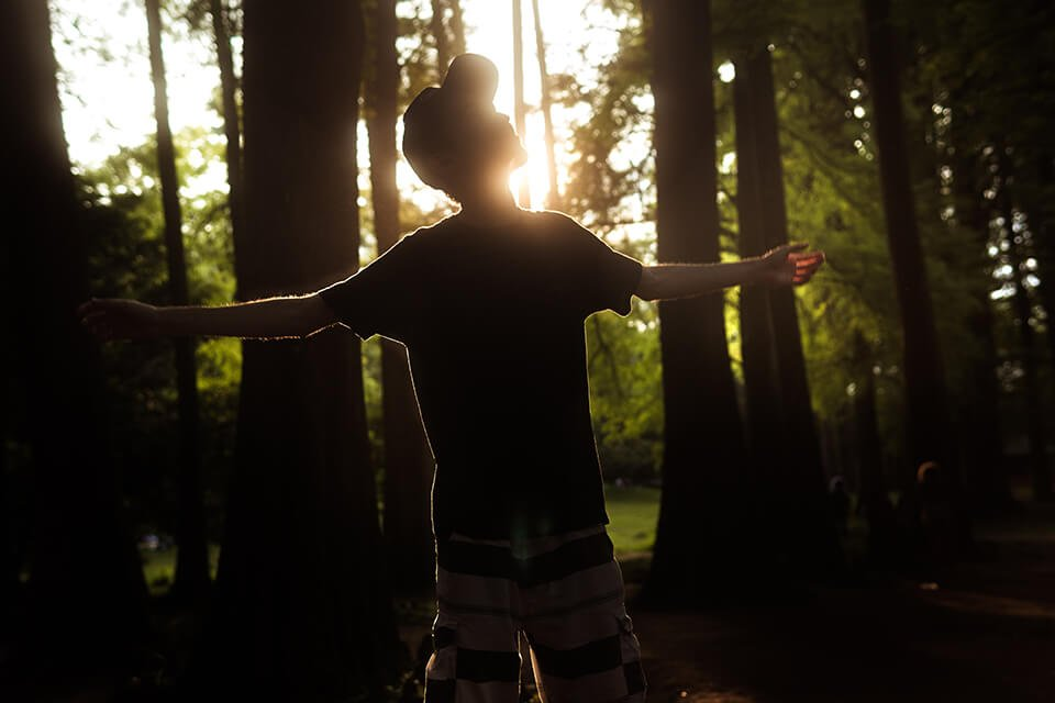 Man with his arms open, looking up in the middle of a forest